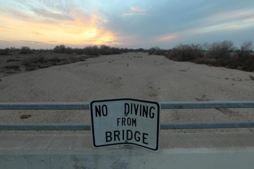LOS ANGELES, CA - FEBRUARY 4: A sign from wetter times warns people not to dive from a bridge over the Kern River, which has been dried up by water diversion projects and little rain, on February 4, 2014 in Bakersfield, California. Now in its third straight year of unprecedented drought, California is experiencing its driest year on record, dating back 119 years. Grasslands that support cattle have dried up, forcing ranchers to feed them expensive supplemental hay to keep them from starving or to sell at least some of their herds, and farmers are struggling with diminishing crop water and what to plant or whether to tear out permanent crops which use water year-round such, as almond trees. About 17 rural communities could run out of drinking water within several weeks and politicians are are pushing to undo laws that protect several endangered species. (Photo by David McNew/Getty Images)
